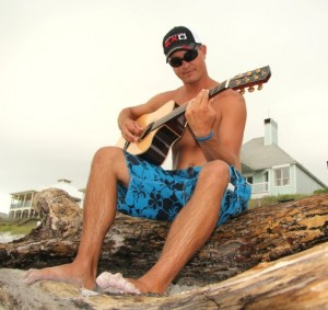 Casey Ashley with his guitar on the beach